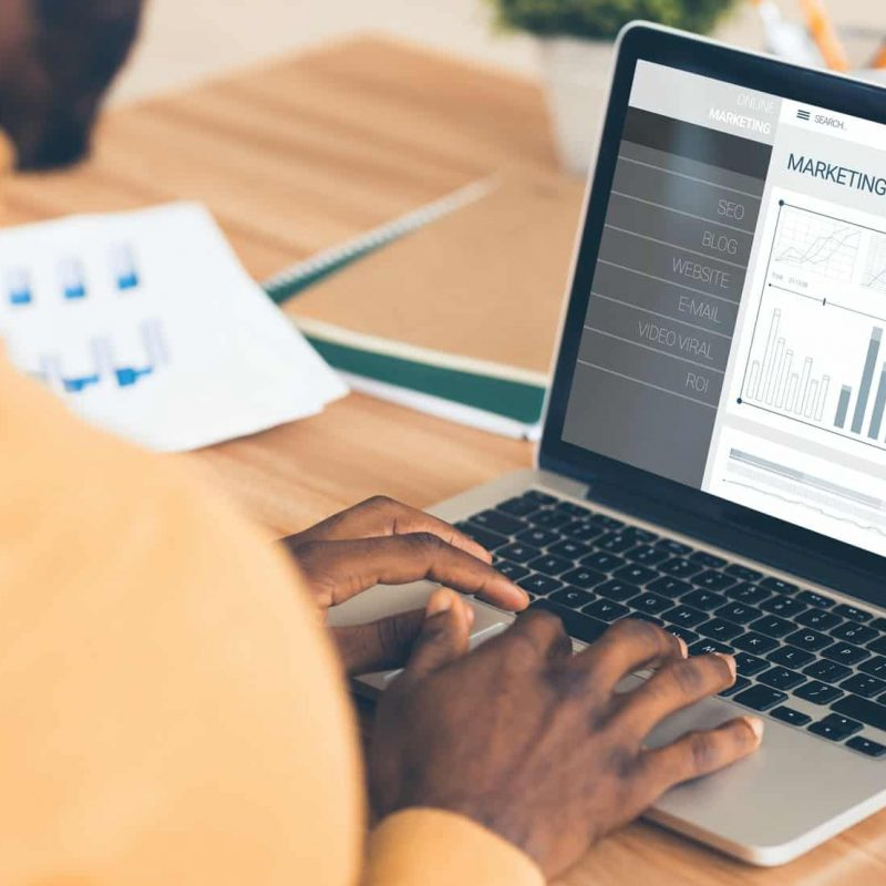 Businessman At Laptop Working With Internet Marketing Charts In Office